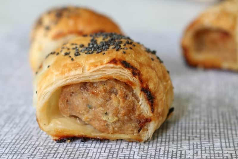 A close up  of a golden baked sausage roll with poppy seeds sprinkled on top.