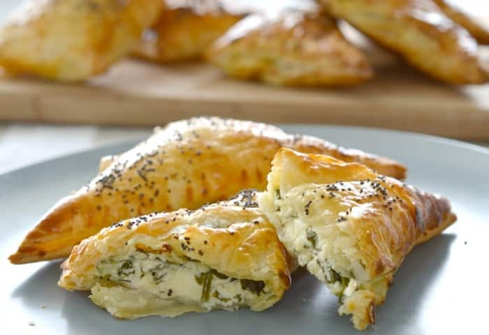 Golden pastry triangles with one split to show a spinach and cheese filling.