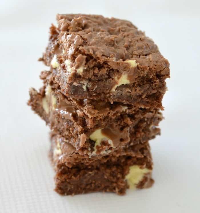 A stack of three pieces of a chocolate slice with chunks of white chocolate inside.