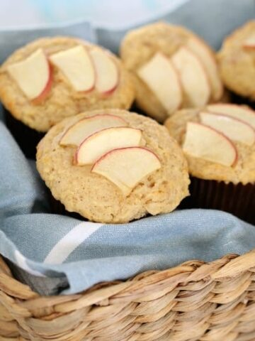A basket filled with muffins in cases, with slices of apple baked on top.