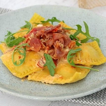 A grey dish filled with a serve of ravioli made with pumpkin and garnished with rocket leaves and crispy prosciutto.