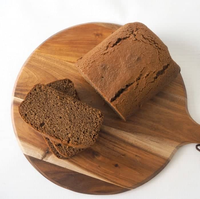 A round wooden board with a gingerbread loaf on it, with two slices cut.