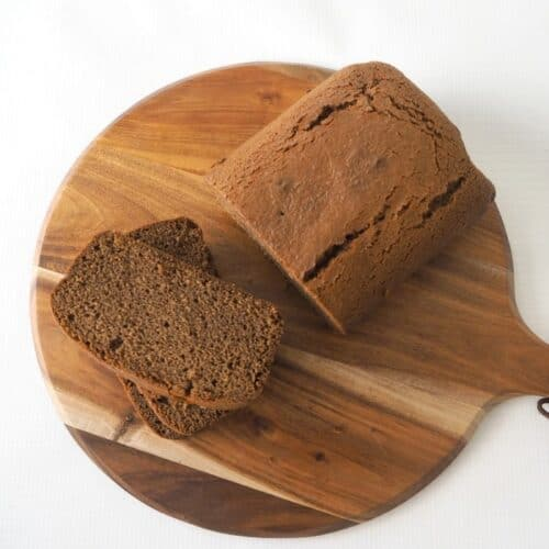 A gingerbread loaf with two slices cut, resting on a round wooden serving board.