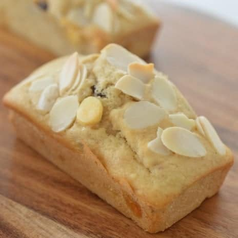 A close up of a mini loaf baked with white chocolate and cranberries, with flaked almonds on top.