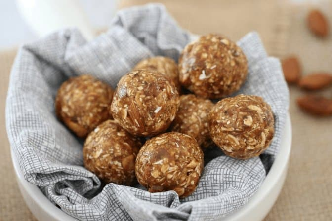 A pile of healthy bliss balls filled with oats, nuts and dates on a tea towel.