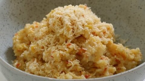 A grey bowl filled with a rice risotto made with chicken and leek, and grated parmesan on top.