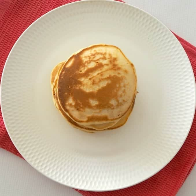 An overhead shot of a stack of golden pancakes on a white plate.