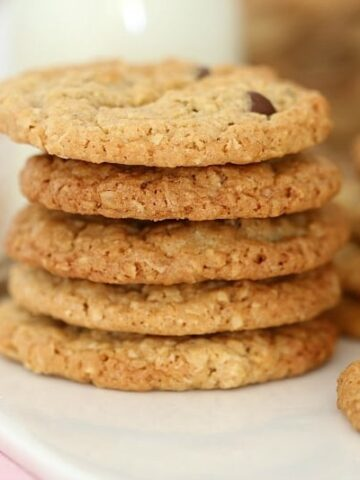 A close up of a stack of oat cookies made with chocolate chips