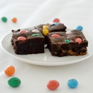 Mini pastel coloured Easter eggs baked on top of a brownie slice, served on a plate.