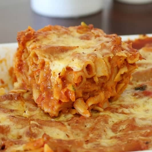 A close up of a tomato based pasta bake with lots of vegetables and cheese cooked through it.