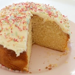 A round golden butter cake with white frosting and sprinkles, with one piece removed to show texture inside.