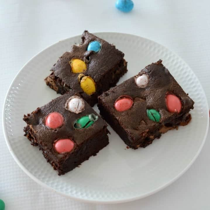 Three pieces of a chocolate brownie slice with coloured Easter eggs baked on the top, served on a white plate