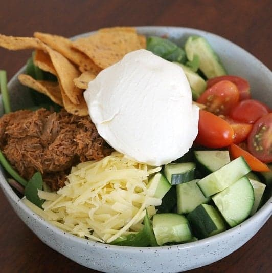 A bowl filled with corn chips, spinach leaves, chopped tomatoes and cucumber, beef and grated cheese, and a dollop of sour cream on top.