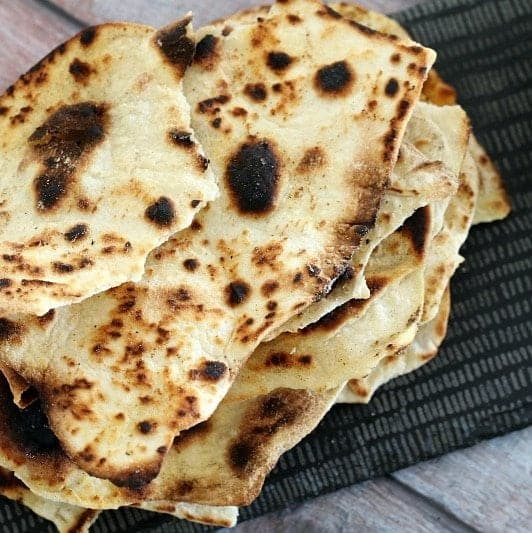 A stack of baked roti bread torn into pieces.