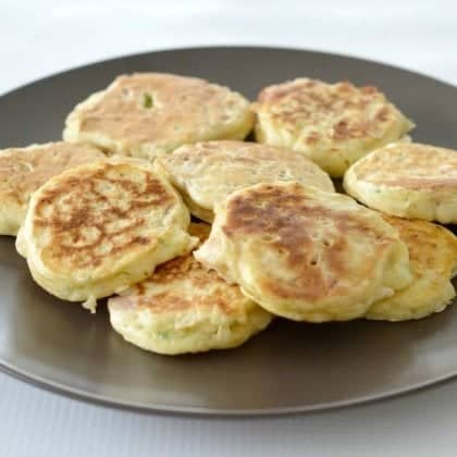 A batch of ham and zucchini pikelets served on a black plate.