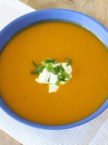 A dollop of sour cream and chopped chives in the middle of a bowl of creamy pumpkin soup.