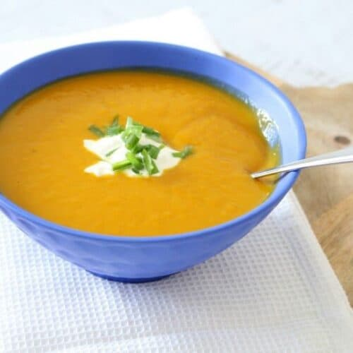 A blue bowl filled with creamy pumpkin soup with a dollop of sour cream and chopped chives on top.