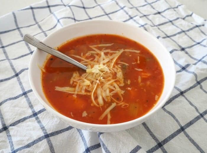 A spoon in a bowl of tomato and vegetable soup with cheese grated on top.