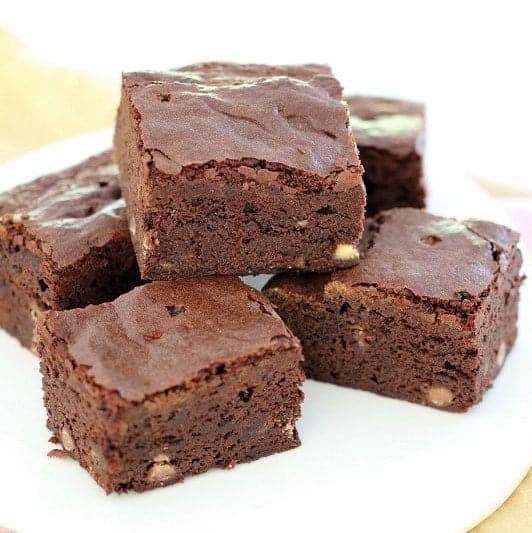 A pile of five chocolate brownie squares with white chocolate chips inside, on a white plate.