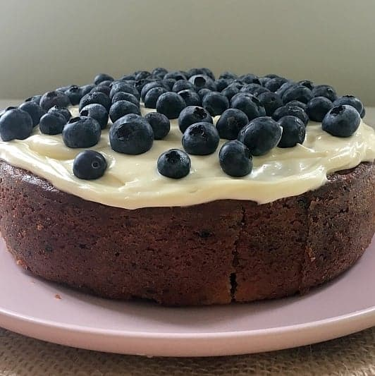 Blueberries and white frosting over the top of a round blueberry and lemon cake.