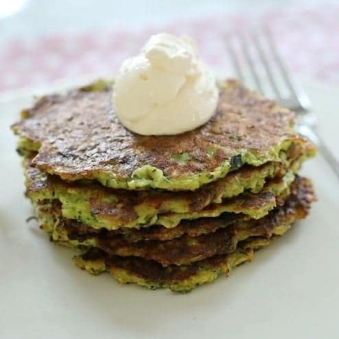 A stack of zucchini fritters topped with a dollop of sour cream.