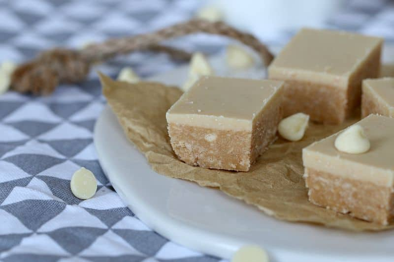 Squares of a peanut butter slice with a peanut butter and white chocolate topping, sitting on baking paper.