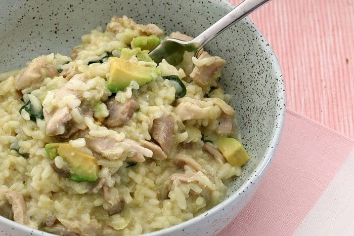 A bowl of creamy white risotto full of chicken, mushrooms and avocado pieces.