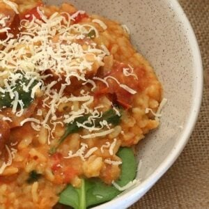 Creamy risotto made with cherry tomatoes and chorizo, resting on baby spinach leaves in a bowl.