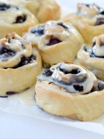 A batch of baked scrolls with blueberries rolled through them, and drizzled with white icing on top.
