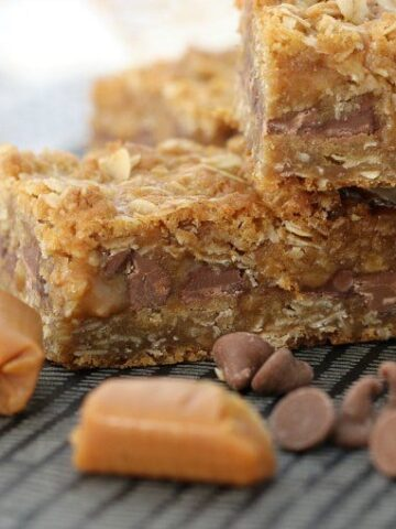 Caramels and chocolate chips in front of pieces of a slice made with oats, caramels and chocolate chips.