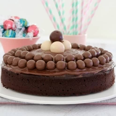 A round chocolate cake with chocolate frosting, decorated with Malteser balls and white Lindt balls on top.