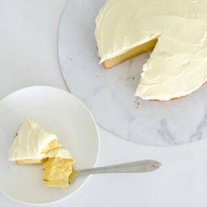 A slice of a white chocolate cake topped with white frosting, on a plate, with the remaining cake beside it.