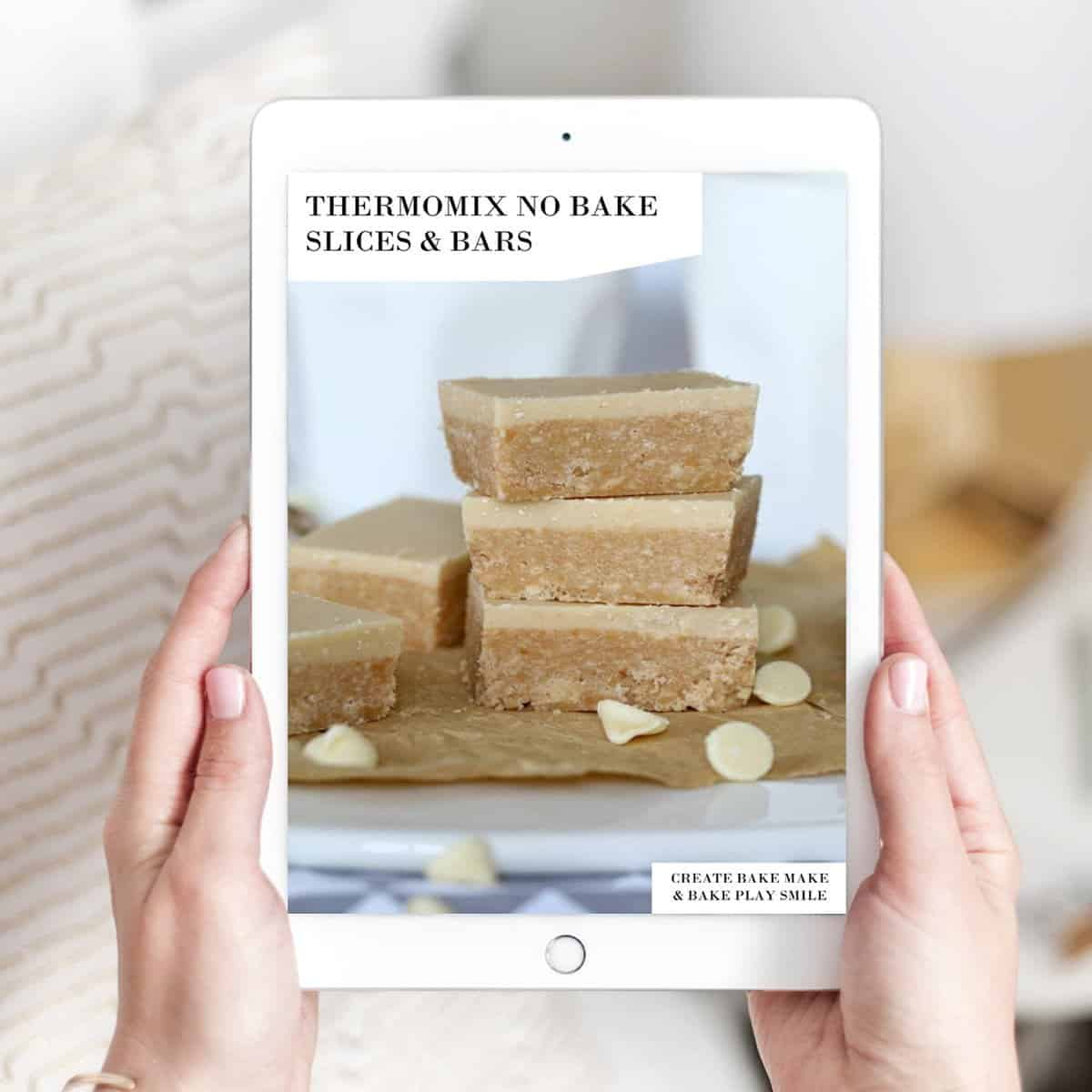 Two hands holding a recipe book - Thermomix No Bake Slices and Bars