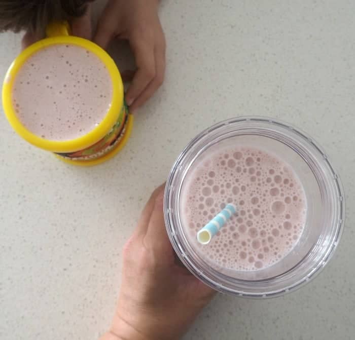 An overhead shot of hands holding glasses of frothy strawberry smoothies.