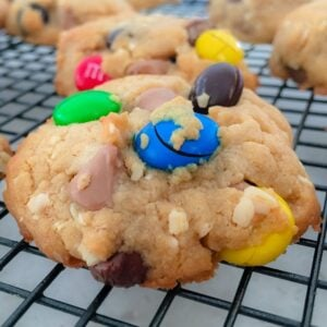 Cookies loaded with colourful M&M's cooling on a black wire tray.