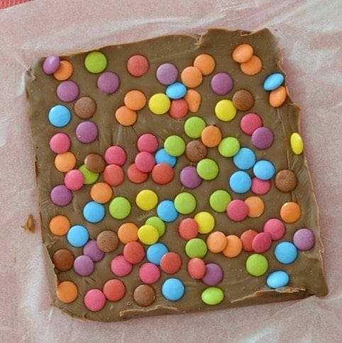 A slab of fudge covered with coloured Smarties all over the top.