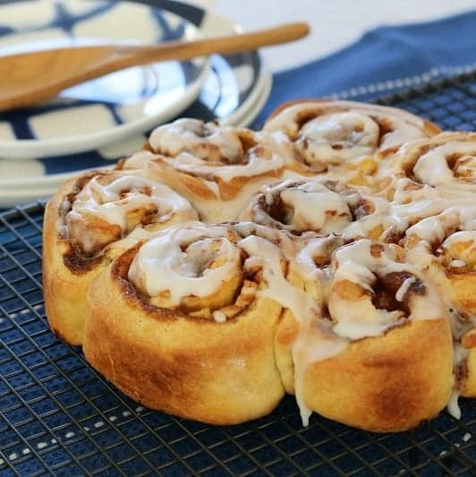 A round of golden scrolls made with apple and cinnamon rolled inside, and drizzled with white icing.