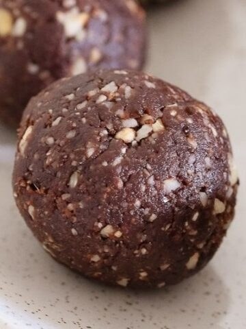 A close up of a round chocolate and hazelnut bliss ball.