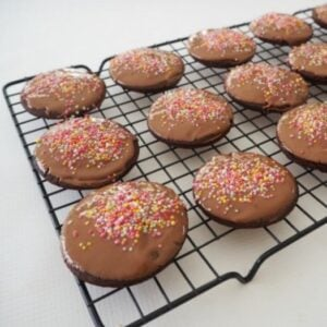 Chocolate biscuits with sprinkles on top cooling on a black wire rack.
