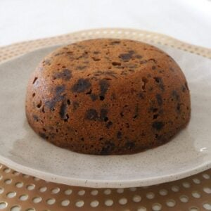 A white plate with a Christmas pudding on it.