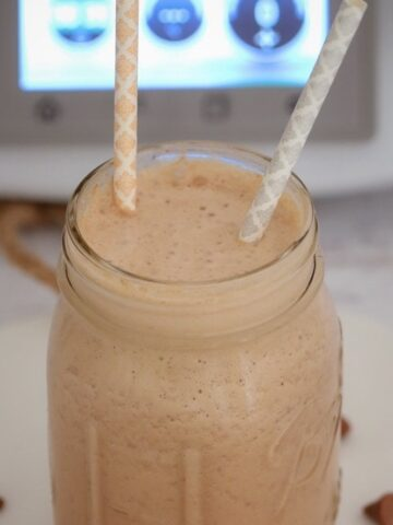 A jar with two straws in it, filled with a creamy chocolate drink.