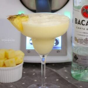 A piece of pineapple on the edge of a creamy cocktail in a stemmed cocktail glass, with a bottle of Bacardi next to it.