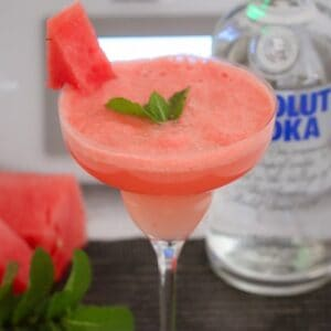 A stemmed cocktail glass with a slushy pink drink garnished with a piece of watermelon and a sprig of mint.