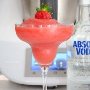 A slushy strawberry drink served in a stemmed cocktail glass with a strawberry on top, and a bottle of vodka nearby.