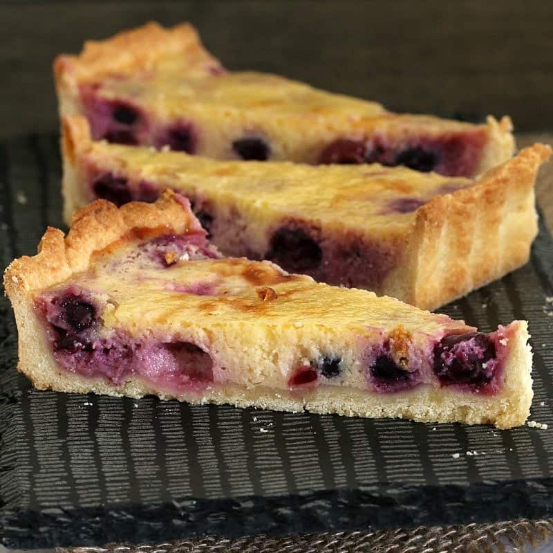 Three wedges of a lemon and blueberry tart made with shortcrust pastry.