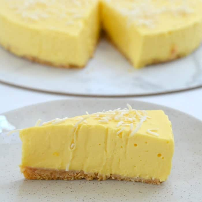 A serve of a creamy cheesecake made with mango on a plate, with the remaining cheesecake in the background.