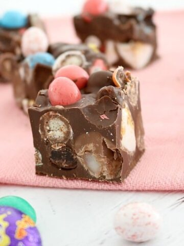 A close up of a piece of Rocky Road filled with mini Easter eggs throughout, and mini coloured Easter eggs on top.