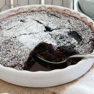 Chocolate sauce showing under a chocolate pudding baked in a round baking dish.