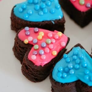 Pieces of a chocolate brownie slice, cut into heart shapes and decorated with pink and blue icing and coloured cachous balls
