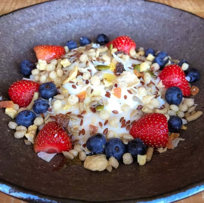 A bowl of porridge with strawberries, blueberries, nuts and seeds on it.